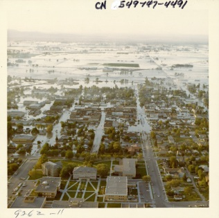 Looking north over downtown Rexburg, Idaho, 14 mi SW of Teton Dam. Ricks College, today Brigham Young University - Idaho, in the foreground and located on a hill was untouched by the flood. The Mormon Church provided food and shelter there in the critical first few days after the disaster (NAID 28894686)