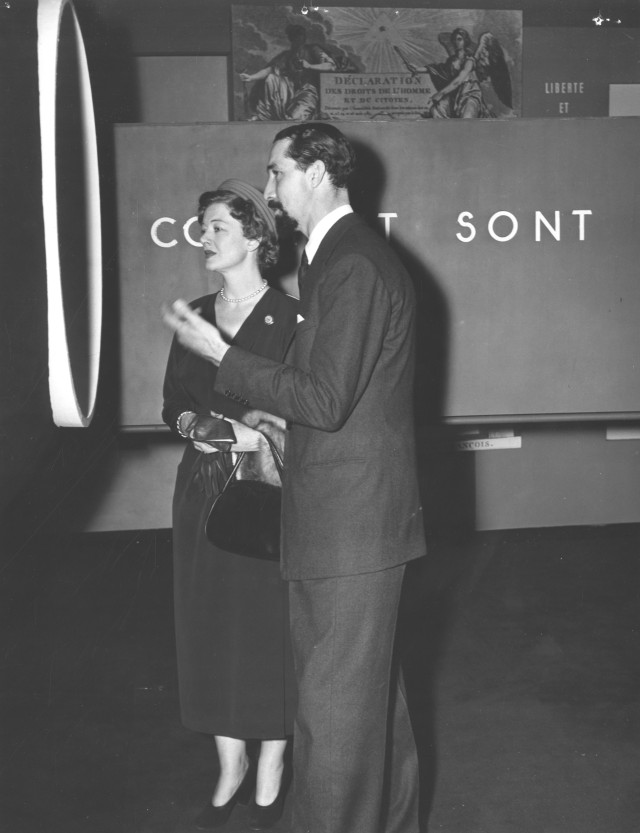 This is a photograph of Miss Myrna Loy, American film star in Paris for the conferences is being shown the Exhibit of Human Rights by Clive Entwistle.