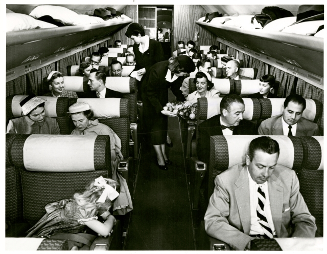 Photograph of a full airplane cabinet, with stewardesses walking the aisles serving the passengers.