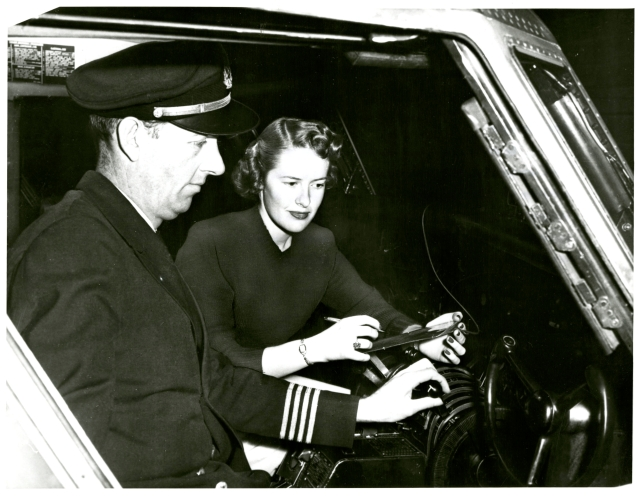 A stewardess and pilot in the cockpit.